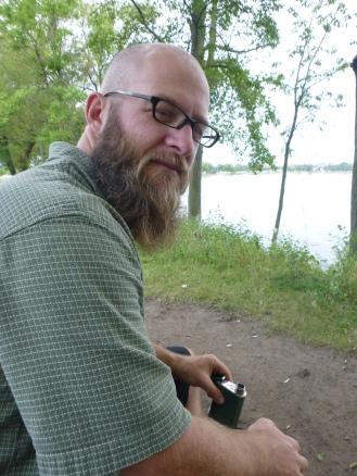 Beard on a bench with bourbon.